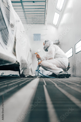 Fotomural  Worker painting a car in a paint chamber, low angle view.
