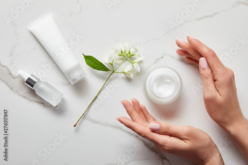 Fotografie, Obraz  top view of woman hands near cosmetic glass bottle, jar with cream, moisturizer