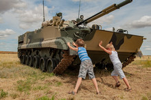 Two Children In Bright Clothes Are Pushing Away Modern Battle Tank. Children Play Until Tankists Arrive. Concept Of Contrasting Innocent Childhood And War