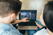 Couple Choosing New House Using Laptop. Scrolling The Internet In Search Of New Estate