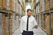 portrait friendly businessman/ manager in suit working in the warehouse of a company - control of inventories