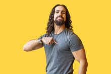 Portrait Of Proud Bearded Young Man With Long Curly Hair In Grey Tshirt Standing, Pointing Himself And Looking At Camera With Confident Serious Face. Indoor Studio Shot Isolated On Yellow Background.