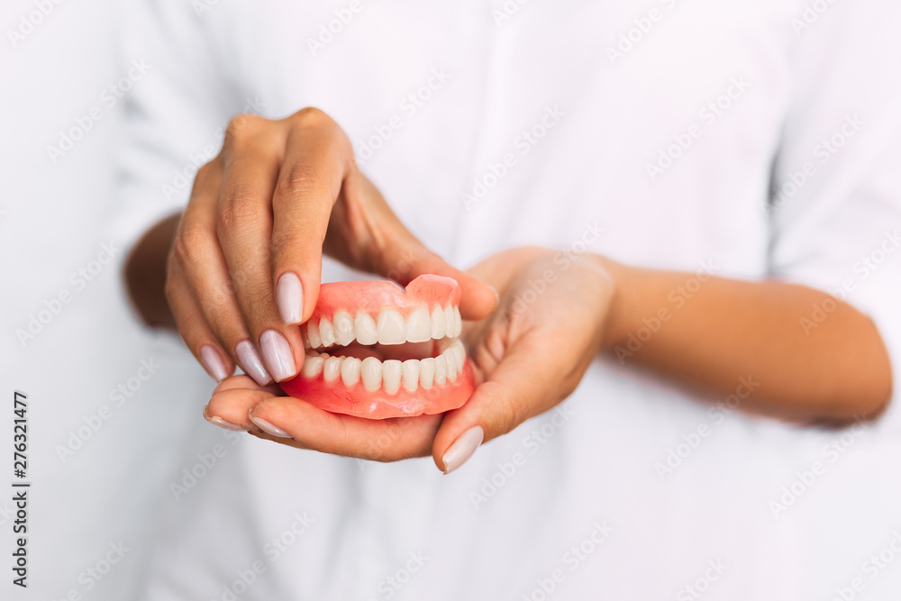 Fototapety, obrazy: The dentist is holding dentures in his hands. Dental prosthesis in the hands of the doctor close-up. Front view of complete denture. Dentistry conceptual photo. Prosthetic dentistry. False teeth