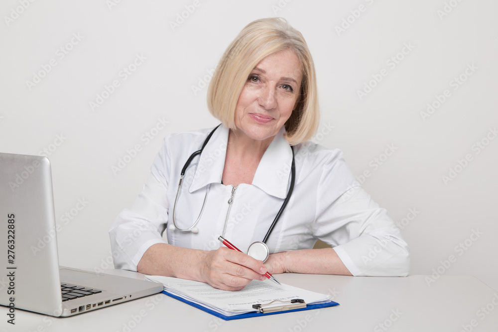 Fototapety, obrazy: Woman doctor in a white medical clothes sitting in cabinet and working on a laptop