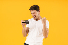Photo Of Happy Man In Basic T-shirt Rejoicing While Playing Video Game On Smartphone