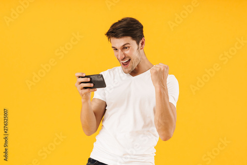 Photo of happy man in basic t-shirt rejoicing while playing video game on smartp Poster Mural XXL