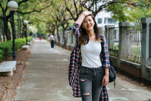 Attractive Young Asian Woman Enjoying Time Outside In Park With Sunshine. College Girl Going To University On The Way Walking Fast With Wind Blowing And Flicks Her Hair Carrying Backpack Outdoors.