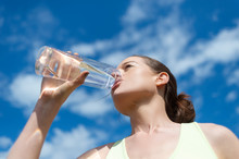 Woman Drinking Water From A Glass Bottle