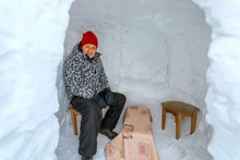 Beautiful Mature Man Sits In A Snowy Igloo And Meets The New Year