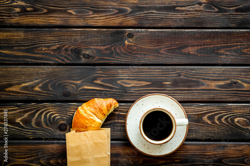 Fotografia, Obraz Fresh pastry with croissant in paper bag and cup of coffee on wooden background
