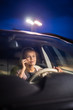 Young female driver playing with her cellphone instead of paying attention to driving startled in a potentially dangerous situation - Road safety concept