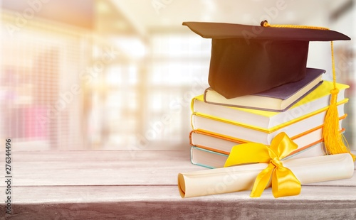Stampa su Tela  Graduation mortarboard on top of stack of books on  background