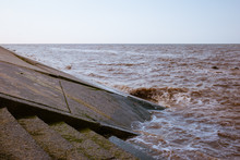 Sea Water And Waves Hitting A Sloping Concrete Revetment Or Seawall As Part Of The Coastal Flood Defences