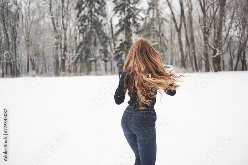 Over there, where our car is. Rear view of girl with long hair runs near the forest to the automobile in wintertime