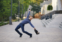 Crazy Young Businessman Dancing On The Street With Bag. Celebrating Victory. Flexibility And Grace In Business