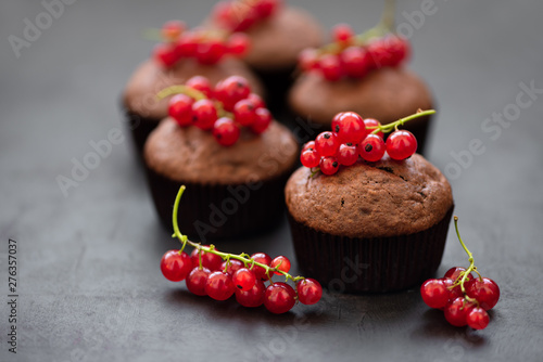 Deurstickers Dessert Chocolate muffins decorated red currant berries on dark wooden background. Flat lay. Soft focus