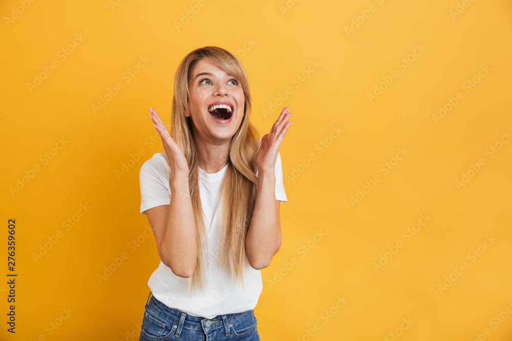 Fototapeta Happy young excited shocked blonde woman posing isolated over yellow wall background.