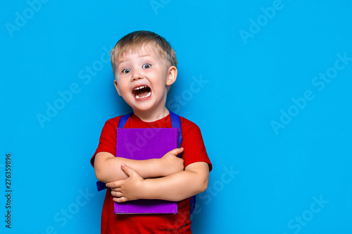 Fotografie, Obraz  shouting boy with book and schoolbag, upset surprised and afraid of school