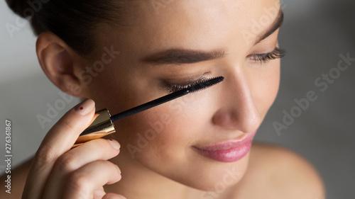 Valokuva  Woman Applying Black Mascara on Eyelashes with Makeup Brush