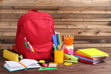 Backpack With School Supplies On Brown Wooden Table