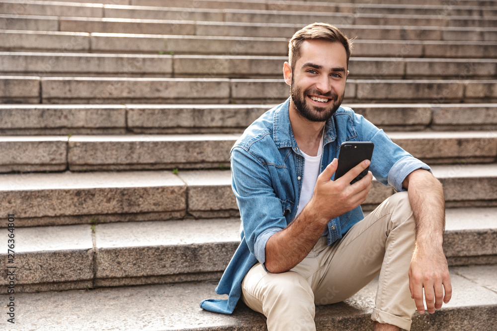 Fototapety, obrazy: Smiling young man sitting on stairs outdoors