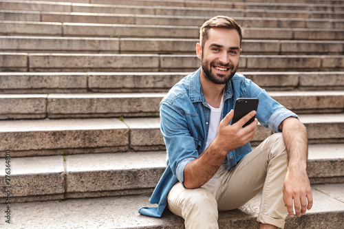 Smiling young man sitting on stairs outdoors - 276364801