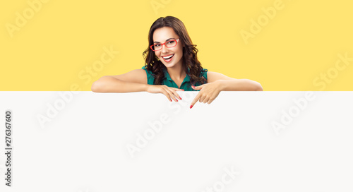 Obraz Happy smiling beautiful young woman in green clothing and red glasses, pointing blank white bill board or copy space empty place for ad slogan or sign text, over yellow color background - fototapety do salonu