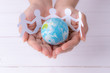 Leinwanddruck Bild Closeup woman hands holding globe with white people chain made from paper cut. World population day.