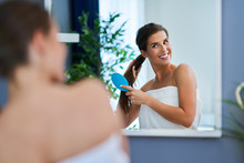 Happy Woman Brushing Hair In B...