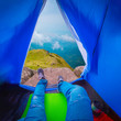 canvas print picture - Close up of young man wearing blue jeans while enjoying the view of mountain range with blue sky and cloudy sky background, View from inside a blue tent - Image