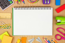 Blank Coil Notebook With School Supplies Frame Against A Wood Desk Background. Back To School Concept. Copy Space.