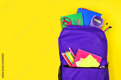 Obraz Purple backpack full of school supplies against a bright yellow background. Close up, top view with copy space. - fototapety do salonu