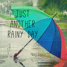 Just Another Rainy Day - Inspiration Quote. Colorful Umbrella In Rainy Weather. Rainbow Umbrella, View From Wet Window. Water Drops Texture. Abstract Blurred Rainy Autumn Season. Soft Selective Focus
