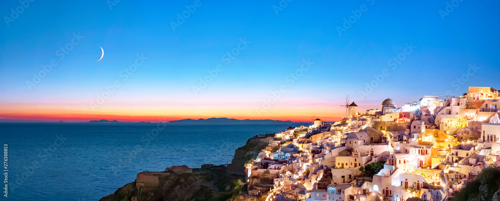 Fototapeta Oia at sunset. Beautiful panoramic view of the village of Oia, Santorini, Greece, Aegean sea, Europe. Classic white Greek architecture, houses, churches, windmills. Night view, moon in the sky