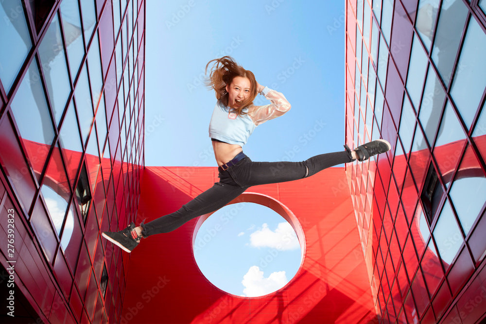 Fototapety, obrazy: Fit woman jumping on urban red background - Image