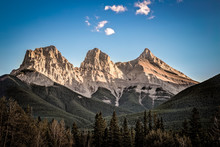 Looking Over A Pine Tree-line Towards The Three Sisters Mountain Peaks In Canmore Alberta At Sunset With A Deep Blue Sky And A Few White Clouds.
