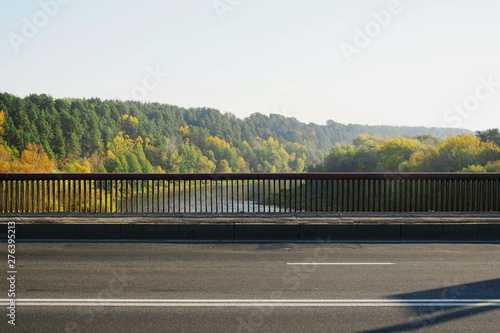 side view of railing of large wide bridge over river, empty asphalt highway fore Fototapete
