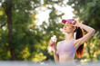 Beautiful slim brunette woman drinking water from bottle after running at the morning park to stay hydrated. Female fitness model working out outdoor. Concept of healthy lifestyle.