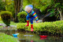 Child With Paper Boat In Puddle. Kids By Rain.