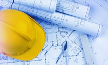 Blueprints Construction And A Yellow Hardhat With A Compass