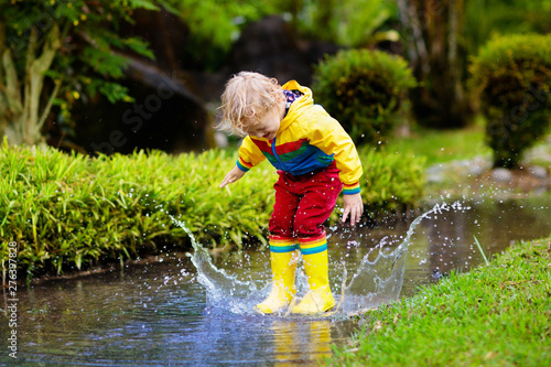 Fotografia Child playing in puddle. Kids jump in autumn rain