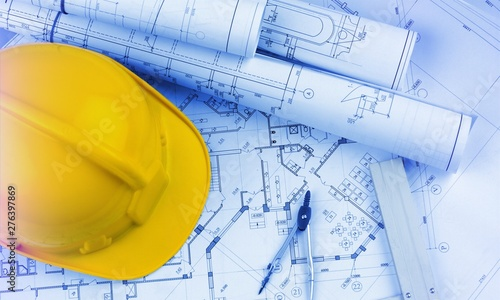 Obraz Blueprints construction and a yellow hardhat with a compass - fototapety do salonu