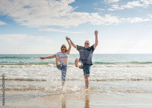 Senior couple in love walking on the beach having fun in a sunny day Tableau sur Toile