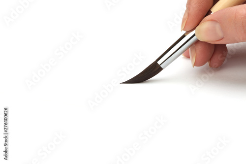 Hand with paint brush on white background