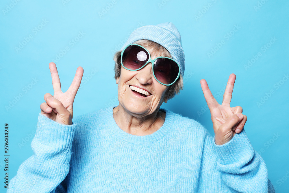Fototapety, obrazy: Funny old lady wearing blue sweater, hat and sunglasses showing victory sign. Isolated on blue background.