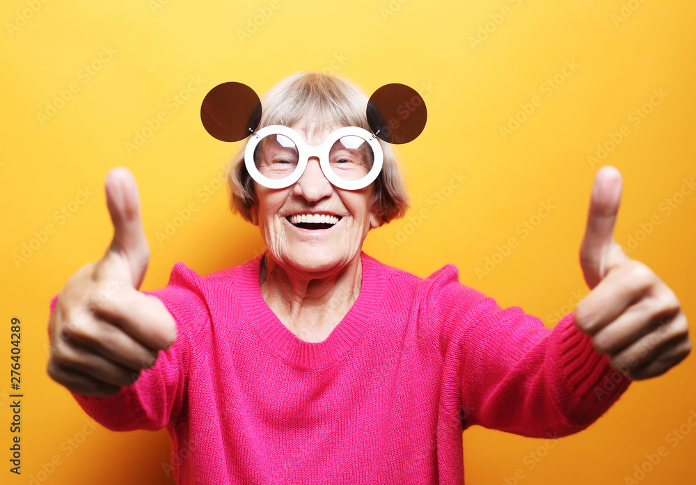 Fototapeta Lifestyle, emotion and people concept: Funny old lady wearing pink sweater and sunglasses showing ok sign