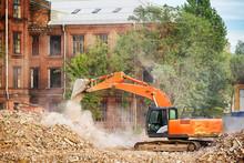 Orange Excavator Working On The Ruins Of A Demolished Building