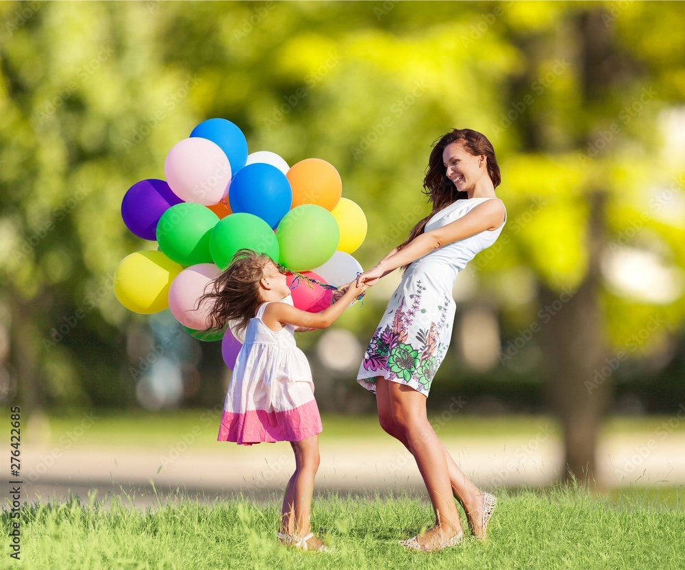 Fototapety, obrazy: Beautiful happy mother with daughter having fun in green field holding colorful balloons