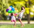 Leinwandbild Motiv Beautiful happy mother with daughter having fun in green field holding colorful balloons