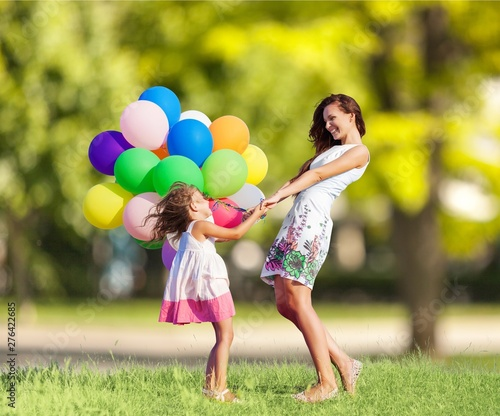 Montage in der Fensternische Logo Beautiful happy mother with daughter having fun in green field holding colorful balloons